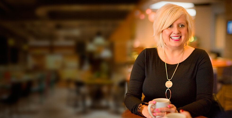 Christi Bintliff sitting while smiling and wearing a gold necklace with a black shirt
